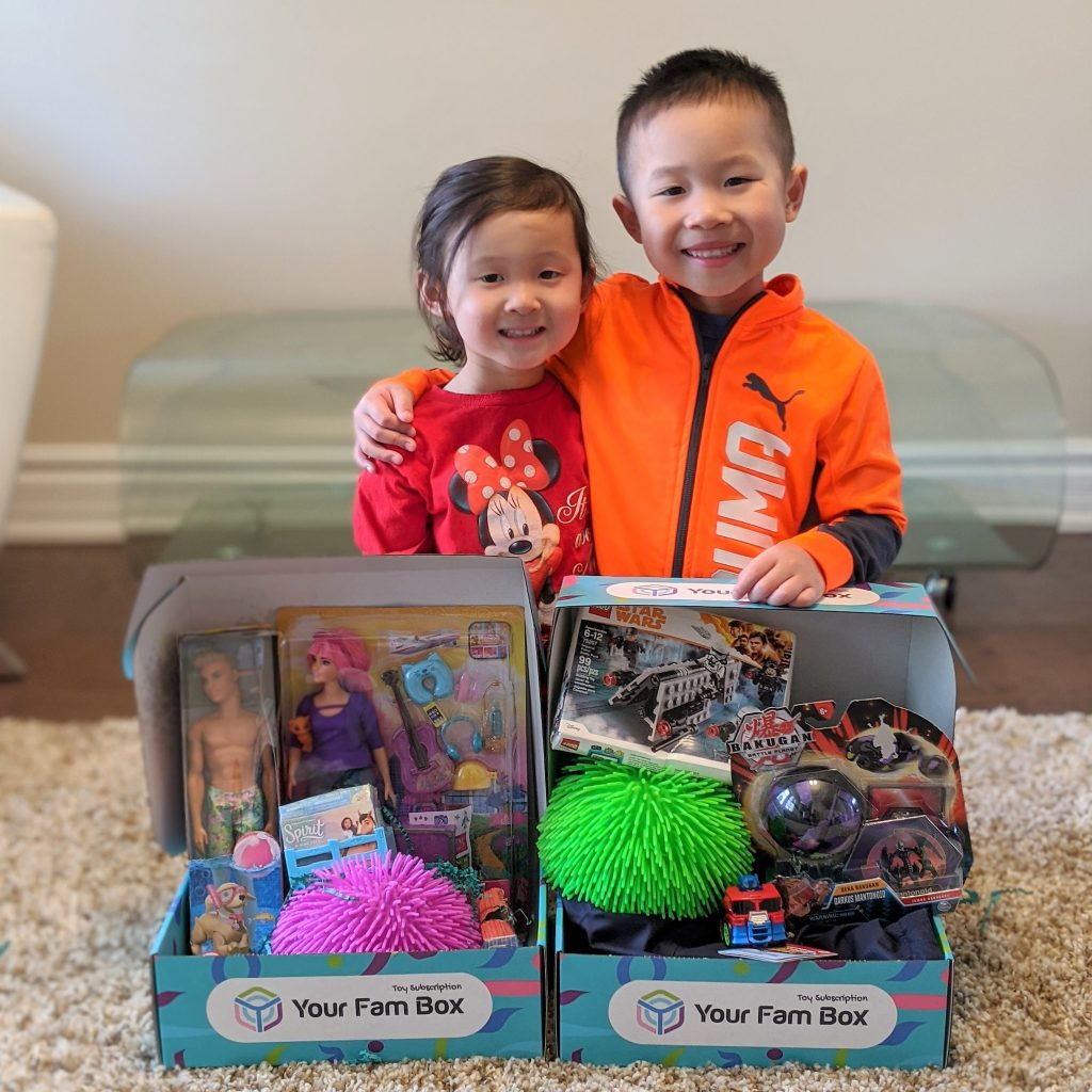 A young boy and girl standing in front of two boxes of toys filled with barbies, monster trucks, etc.
