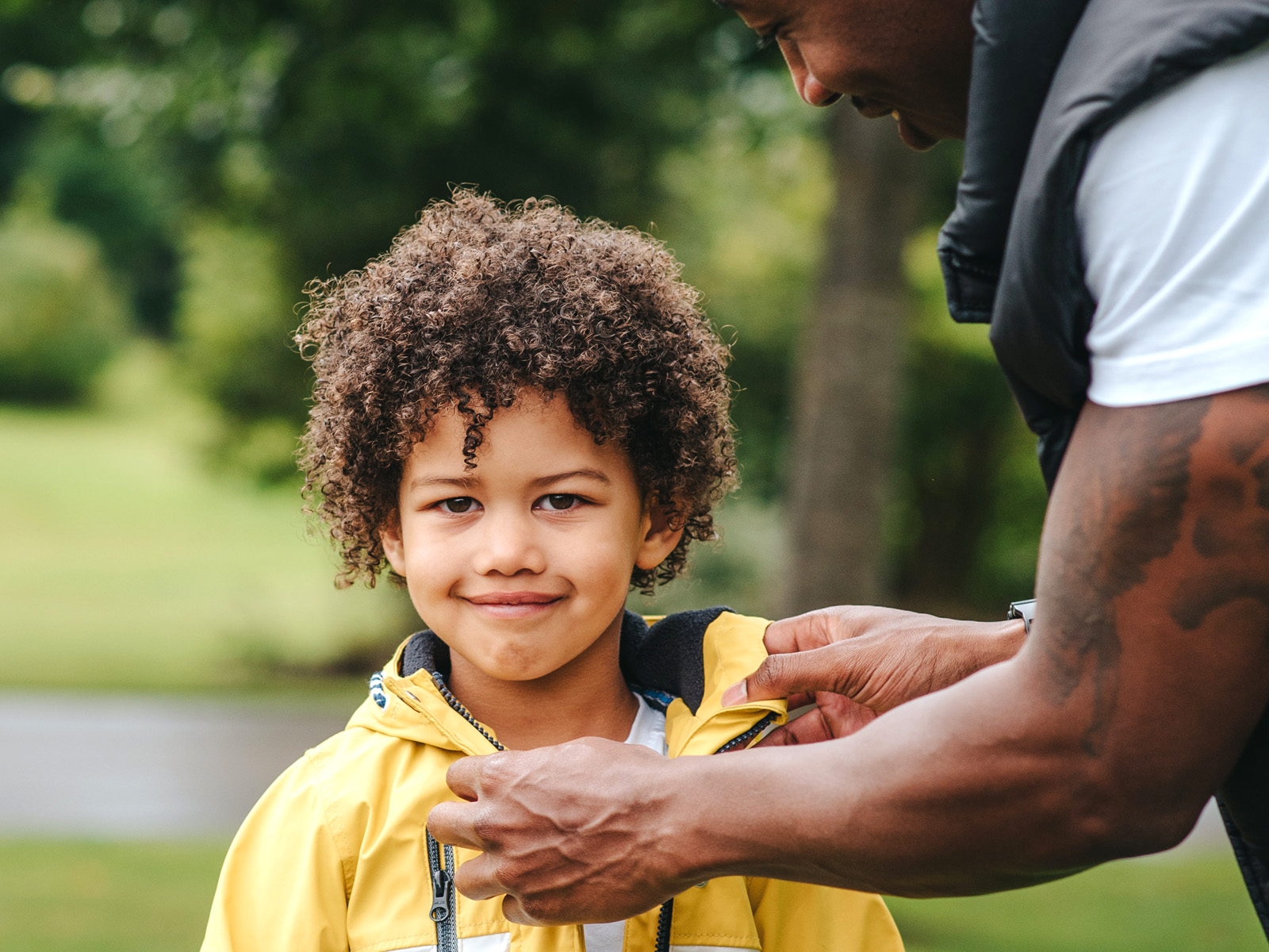 Young boy getting assistance from a parent zipping up his coat
