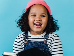 Little girl in pink hat laughing