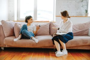 Doctor and teenage girl talking on a couch.